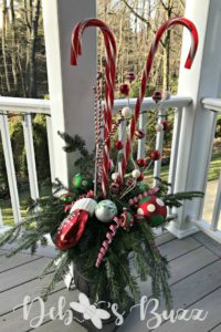 On the covered back deck, during the holidays, is a whimsical pair of lighted, candy cane Christmas urns.